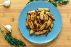 Ψημένες πατάτες με το αλατισμένα πιπέρι και το κύμινο στο ξύλινο υπόβαθρο Στοκ Φωτογραφία