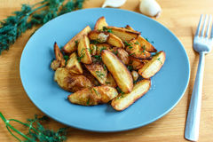 Ψημένες πατάτες με το αλατισμένα πιπέρι και το κύμινο στο ξύλινο υπόβαθρο Στοκ Εικόνες