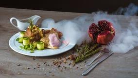 Ψημένες πατάτες με το κοτόπουλο κάτω από τη ρόδινη σάλτσα, ρόδι, καπνός στοκ φωτογραφία