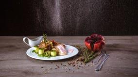 Ψημένες πατάτες με το κοτόπουλο κάτω από τη ρόδινη σάλτσα, ρόδι, ψεκασμός του νερού στοκ φωτογραφία με δικαίωμα ελεύθερης χρήσης