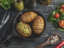 Ψημένες ψημένες πατάτες πλήρως στο δέρμα, σαλάτα Τηγάνι χυτοσιδήρου στον πίνακα στοκ εικόνες με δικαίωμα ελεύθερης χρήσης