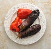 Ψημένες πιπέρια και μελιτζάνα σε ένα πιάτο σε ένα μαρμάρινο υπόβαθρο Στοκ φωτογραφία με δικαίωμα ελεύθερης χρήσης