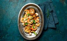 Ψημένες στη σχάρα ψημένες γαρίδες γαρίδων στο ωοειδές εκλεκτής ποιότητας πιάτο μετάλλων, κορυφή vie Υπόβαθρο πλακών Στοκ εικόνα με δικαίωμα ελεύθερης χρήσης