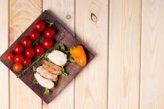 Ψημένες στη σχάρα λωρίδες κοτόπουλου με την ντομάτα και το πιπέρι στο ξύλινο πιάτο διάστημα αντιγράφων στοκ εικόνες