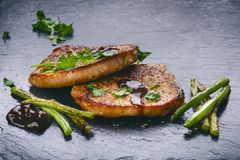 Ψημένες στη σχάρα μπριζόλες χοιρινού κρέατος, μπριζόλες με τα λαχανικά, φασόλια και σάλτσα σε μια μαύρη πλάκα Φρέσκο κρέας με τον Στοκ φωτογραφία με δικαίωμα ελεύθερης χρήσης