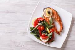 Ψημένες στη σχάρα μπριζόλα και σαλάτα σολομών σε ένα πιάτο οριζόντια τοπ άποψη Στοκ εικόνα με δικαίωμα ελεύθερης χρήσης