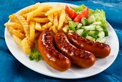 Ψημένες στη σχάρα λουκάνικα και τηγανιτές πατάτες Στοκ εικόνα με δικαίωμα ελεύθερης χρήσης