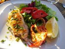 Ψημένες στη σχάρα σουπιές με το λεμόνι, την ντομάτα και το σπανάκι και τη σαλάτα στοκ εικόνα