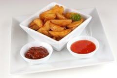 Ψημένες στη σχάρα σφήνες πατατών με την κατ' οίκον γίνοντη πικάντικη σάλτσα Στοκ Εικόνες