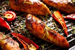 Ψημένες στη σχάρα λωρίδες του κοτόπουλου στο πικάντικο μαρινάρισμα με την προσθήκη του τσίλι σε ένα τηγάνι σχαρών Στοκ Εικόνες
