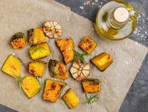 Ψημένες φέτες κολοκύθας με το σκόρδο, το δεντρολίβανο, το ελαιόλαδο και το άλας Στοκ Εικόνες