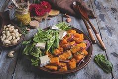 Ψημένες φέτες κολοκύθας, φύλλα σπανακιού, Camembert brie τυρί, τα δυτικά ανακάρδια, σάλτσα χορτοφάγος σαλάτα, πιάτο στοκ εικόνα