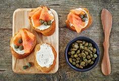 Ψημένες φέτες ψωμιού με το τυρί κρέμας και τον καπνισμένο σολομό Στοκ Φωτογραφία