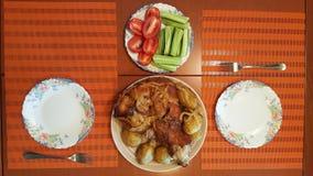 Ψημένη άρθρωση χοιρινού κρέατος με τις πατάτες, τις ντομάτες και τα αγγούρια σε ένα πιάτο για δύο στοκ εικόνες