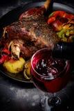 Ψημένη κνήμη αρνιών με τα ψημένα λαχανικά δίπλα στο γυαλί κόκκινου κρασιού Κάθετη εικόνα Στοκ φωτογραφία με δικαίωμα ελεύθερης χρήσης