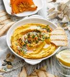 Ψημένη κρεμώδους και εύγευστης εμβύθιση hummus κολοκύθας, σε ένα άσπρο πιάτο στοκ εικόνες με δικαίωμα ελεύθερης χρήσης