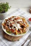 Ψημένη πατάτα με τα πράσινα, το σκόρδο και τις σάλτσες σε ένα άσπρο πιάτο στοκ φωτογραφίες