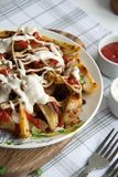 Ψημένη πατάτα με τα πράσινα, το σκόρδο και τις σάλτσες σε ένα άσπρο πιάτο στοκ εικόνες με δικαίωμα ελεύθερης χρήσης