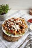 Ψημένη πατάτα με τα πράσινα, το σκόρδο και τις σάλτσες σε ένα άσπρο πιάτο στοκ εικόνες