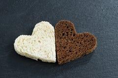 Ψημένη σίκαλη και άσπρο ψωμί υπό μορφή καρδιάς στο Μαύρο στοκ φωτογραφία