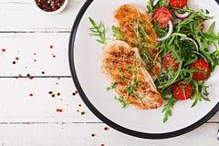 Ψημένη στη σχάρα λωρίδα κοτόπουλου και σαλάτα φρέσκων λαχανικών των ντοματών, του κόκκινων κρεμμυδιού και του arugula Στοκ εικόνες με δικαίωμα ελεύθερης χρήσης