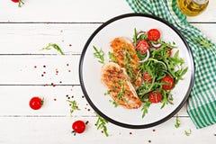 Ψημένη στη σχάρα λωρίδα κοτόπουλου και σαλάτα φρέσκων λαχανικών των ντοματών, του κόκκινων κρεμμυδιού και του arugula Στοκ φωτογραφία με δικαίωμα ελεύθερης χρήσης