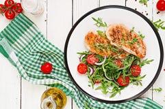 Ψημένη στη σχάρα λωρίδα κοτόπουλου και σαλάτα φρέσκων λαχανικών των ντοματών, του κόκκινων κρεμμυδιού και του arugula Στοκ Εικόνες