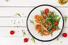 Ψημένη στη σχάρα λωρίδα κοτόπουλου και σαλάτα φρέσκων λαχανικών των ντοματών, του κόκκινων κρεμμυδιού και του arugula Στοκ Φωτογραφίες