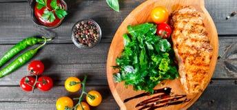 Ψημένη στη σχάρα λωρίδα κοτόπουλου με τη σαλάτα, τις ντομάτες και τη σάλτσα φρέσκων λαχανικών στον ξύλινο τέμνοντα πίνακα στοκ εικόνα