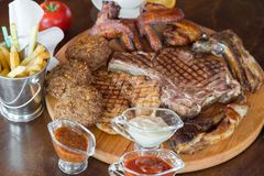 Ψημένη στη σχάρα μπριζόλα βόειου κρέατος και ανάμεικτο εύγευστο ψημένο κρέας στον ξύλινο πίνακα Στοκ φωτογραφία με δικαίωμα ελεύθερης χρήσης