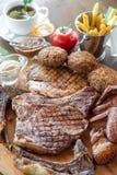 Ψημένη στη σχάρα μπριζόλα βόειου κρέατος και ανάμεικτο εύγευστο ψημένο κρέας στον ξύλινο πίνακα Στοκ Φωτογραφία