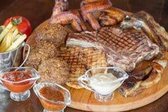 Ψημένη στη σχάρα μπριζόλα βόειου κρέατος και ανάμεικτο εύγευστο ψημένο κρέας στον ξύλινο πίνακα Στοκ Εικόνες