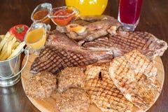 Ψημένη στη σχάρα μπριζόλα βόειου κρέατος και ανάμεικτο εύγευστο ψημένο κρέας στον ξύλινο πίνακα Στοκ Φωτογραφίες
