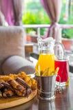 Ψημένη στη σχάρα μπριζόλα βόειου κρέατος και ανάμεικτο εύγευστο ψημένο κρέας με τις τηγανιτές πατάτες και τα δροσερά ποτά στον πί Στοκ Φωτογραφία