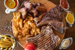 Ψημένη στη σχάρα μπριζόλα βόειου κρέατος, πλευρά αρνιών, φτερά κοτόπουλου με τις τηγανιτές πατάτες και σάλτσες επάνω στον ξύλινο  Στοκ εικόνες με δικαίωμα ελεύθερης χρήσης