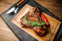 Ψημένη στη σχάρα μπριζόλα βόειου κρέατος σε ένα σκοτεινό ξύλινο επιτραπέζιο υπόβαθρο Στοκ Εικόνα