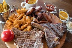 Ψημένη στη σχάρα μπριζόλα βόειου κρέατος, φτερά κοτόπουλου και πασπαλισμένα ραβδιά κοτόπουλου με τις τηγανιτές πατάτες και σάλτσε Στοκ Φωτογραφίες