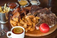 Ψημένη στη σχάρα μπριζόλα βόειου κρέατος, φτερά κοτόπουλου και πασπαλισμένα ραβδιά κοτόπουλου με τις τηγανιτές πατάτες και σάλτσε Στοκ Εικόνες