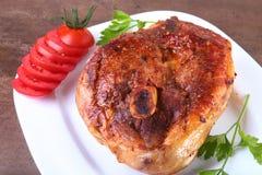 Ψημένη στη σχάρα μπριζόλα χοιρινού κρέατος με την τεμαχισμένη ντομάτα και σάλτσα στον ξύλινο πίνακα Στοκ εικόνες με δικαίωμα ελεύθερης χρήσης
