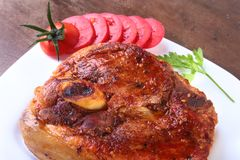 Ψημένη στη σχάρα μπριζόλα χοιρινού κρέατος με την τεμαχισμένη ντομάτα και σάλτσα στον ξύλινο πίνακα Στοκ Εικόνα