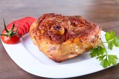 Ψημένη στη σχάρα μπριζόλα χοιρινού κρέατος με την τεμαχισμένη ντομάτα και σάλτσα στον ξύλινο πίνακα Στοκ φωτογραφία με δικαίωμα ελεύθερης χρήσης