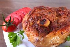 Ψημένη στη σχάρα μπριζόλα χοιρινού κρέατος με την τεμαχισμένη ντομάτα και σάλτσα στον ξύλινο πίνακα Στοκ Φωτογραφίες