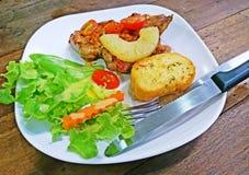 Ψημένη στη σχάρα μπριζόλα χοιρινού κρέατος που τίθεται σε έναν ξύλινο πίνακα Στοκ Εικόνα