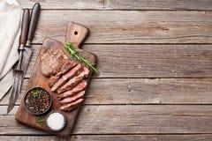 Ψημένη στη σχάρα μπριζόλα βόειου κρέατος με τα καρυκεύματα στον τέμνοντα πίνακα Στοκ εικόνα με δικαίωμα ελεύθερης χρήσης