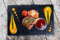 Ψημένη στη σχάρα μπριζόλα βόειου κρέατος με τη φρέσκια σαλάτα και bbq σάλτσα στο υπόβαθρο πλακών πετρών στο ξύλινο υπόβαθρο κοντά Στοκ Εικόνα