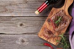 Ψημένη στη σχάρα μπριζόλα βόειου κρέατος με το δεντρολίβανο, το αλάτι και το πιπέρι και το κρασί Στοκ Φωτογραφίες