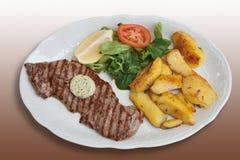 Ψημένη στη σχάρα μπριζόλα γλουτών με τις βουτύρου, τηγανισμένες πατάτες χορταριών Στοκ εικόνα με δικαίωμα ελεύθερης χρήσης