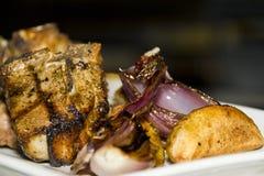Ψημένη στη σχάρα μπριζόλα χοιρινού κρέατος κοντά επάνω με τα κρεμμύδια και τις πατάτες Στοκ εικόνες με δικαίωμα ελεύθερης χρήσης