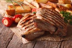 Ψημένη στη σχάρα μπριζόλα χοιρινού κρέατος με τις πατάτες και τα λαχανικά κοντά επάνω στο pape Στοκ εικόνα με δικαίωμα ελεύθερης χρήσης