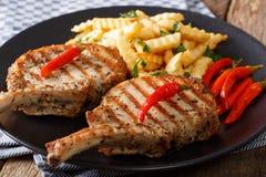 Ψημένη στη σχάρα μπριζόλα χοιρινού κρέατος με το κόκκαλο, το τσίλι και την κινηματογράφηση σε πρώτο πλάνο τηγανητών στο πιάτο Στοκ Εικόνες